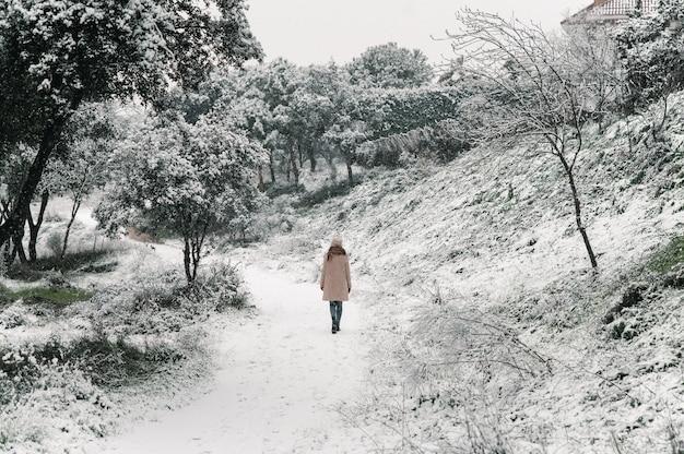Mulher despreocupada com casaco quente e chapéu caminhando ao longo do caminho na floresta enquanto aprecia a natureza no inverno