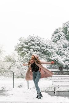 Mulher despreocupada com roupas quentes, virando-se com os braços estendidos enquanto aproveita o dia de neve no inverno no parque
