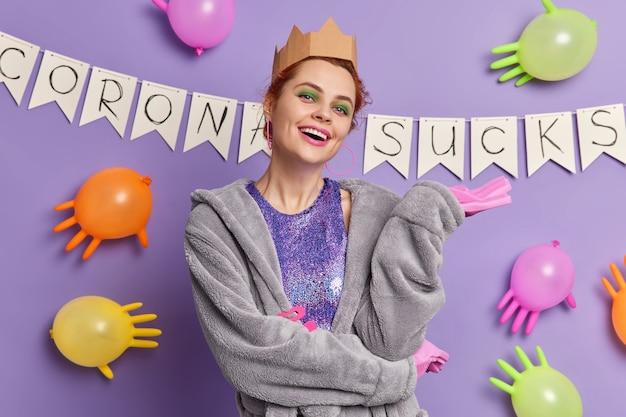 Mulher despreocupada e despreocupada com maquiagem brilhante usa roupão coroa e luvas de borracha e está de bom humor durante poses de festa doméstica contra guirlandas e balões inflados