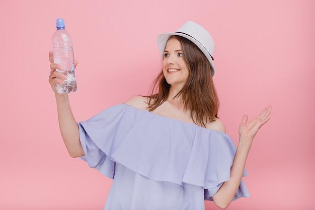 Mulher despreocupada e positiva vestida com um chapéu de palha na moda de verão, beleza natural, segurando uma garrafa de água na mão quente dia de verão sorrindo com bom humor, olha lá fora, longe