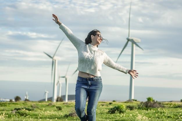 Mulher despreocupada em um campo com moinhos de vento em um dia ensolarado