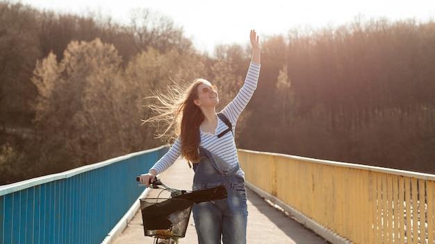 Mulher despreocupada posando com bicicleta na ponte