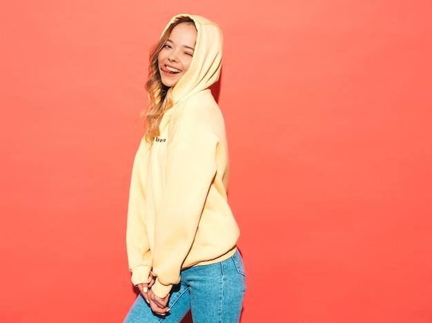 Mulher despreocupada posando perto da parede rosa no estúdio. modelo positivo se divertindo