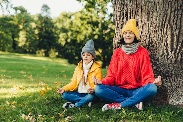 Mulher despreocupada relaxada e filha sentar em pose de lótus perto de árvore no parque, fechar os olhos