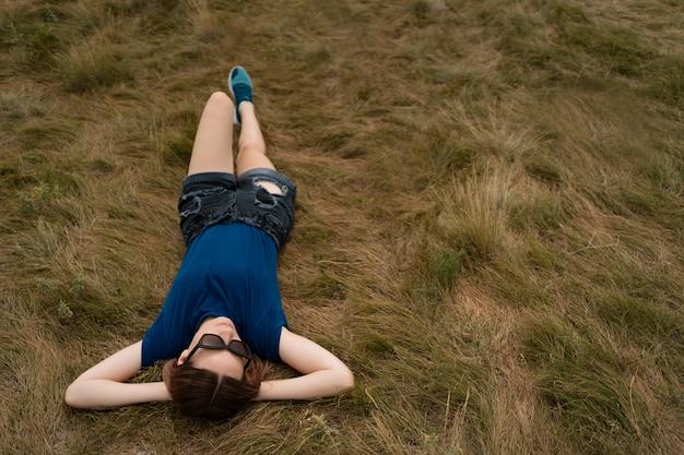 Mulher despreocupada relaxante na grama durante o dia de verão ensolarado, vestindo shorts e óculos.
