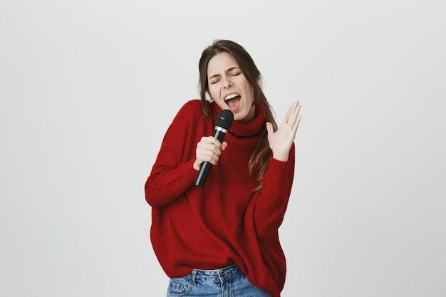 Mulher despreocupada se divertir karaoke, cantando no microfone