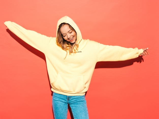Mulher despreocupada sexy posando perto de parede rosa. modelo positivo se divertindo. levantando as mãos
