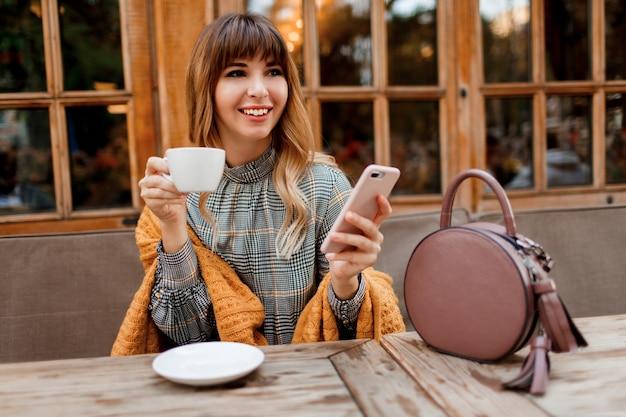 Mulher despreocupada sorridente tem uma pausa para o café em um café aconchegante com interior de madeira, usando telefone celular. segurando uma xícara de cappuccino quente. inverno.