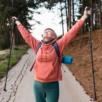 Mulher despreocupada turista sênior com caminhadas varas na floresta