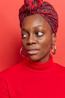 Mulher desvia o olhar com expressão pensativa e usa lenço de gola alta amarrado na cabeça brincos grandes poses em vermelho brilhante