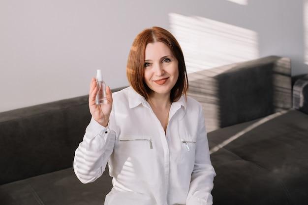 Mulher detém desinfeta spray e olhando para a câmera. mulher adulta usa um limpador de mãos antibacteriano.