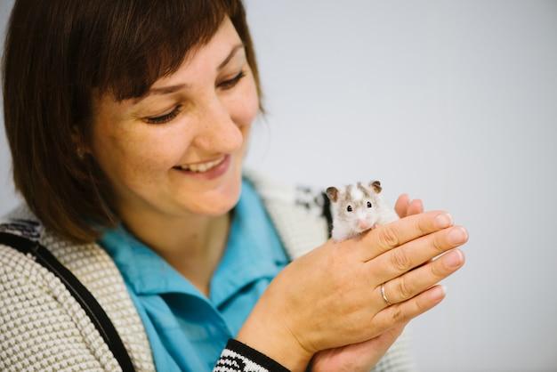 Mulher detém ratinho peludo branco.
