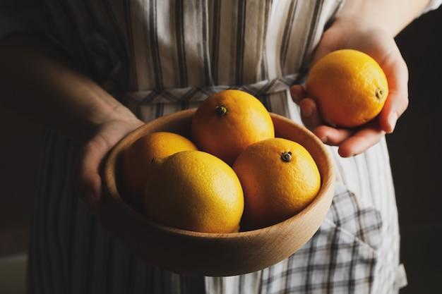 Mulher detém tigela com limões. fruta madura