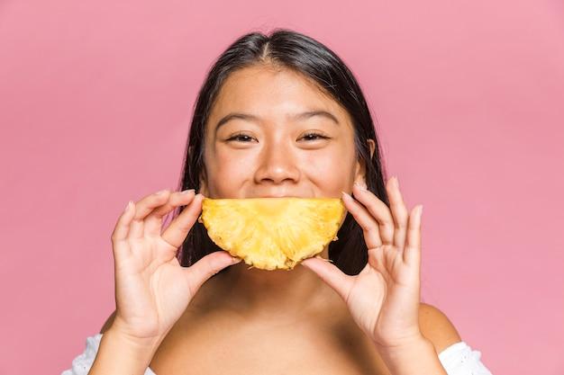 Mulher detém um abacaxi como uma forma sorridente