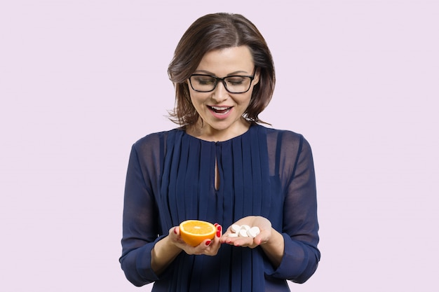 Mulher detém vitamina c laranja e sintética