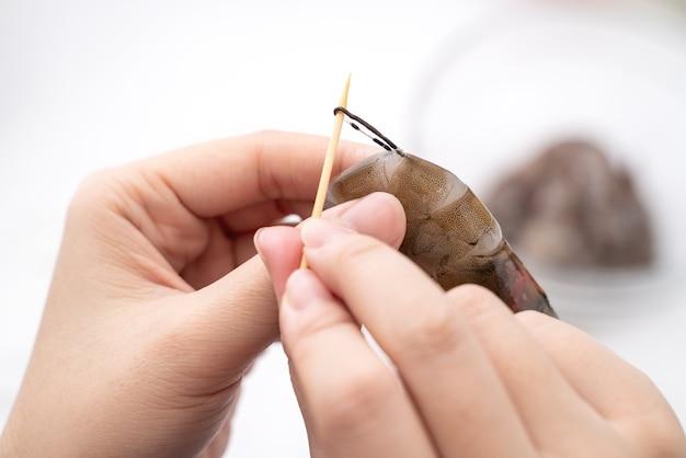 Mulher deveins camarão e puxar a linha do trato intestinal ao cozinhar camarão.
