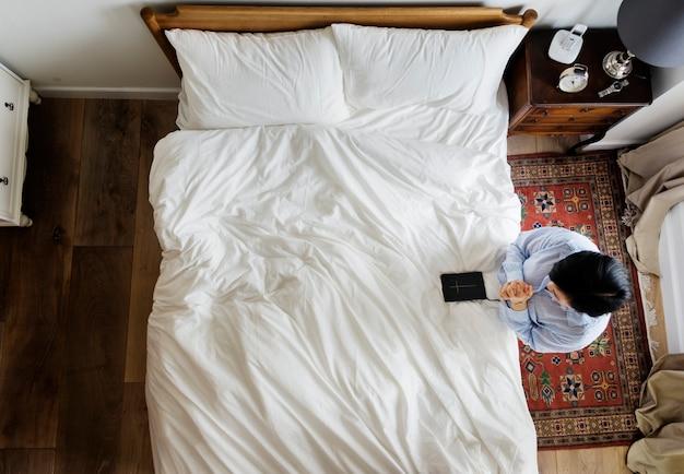 Mulher devota com um livro da bíblia rezando pela cama