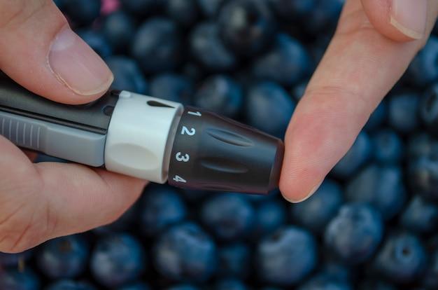 Mulher diabética está tirando sangue de dedo para controle de glicose