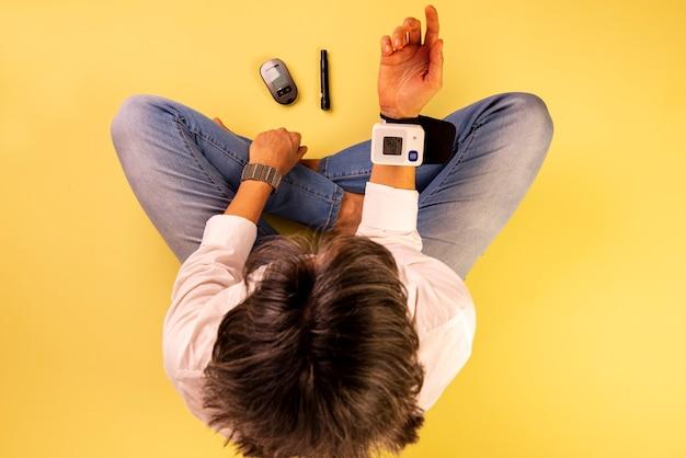 Mulher diabética sentada no chão medindo a pressão arterial