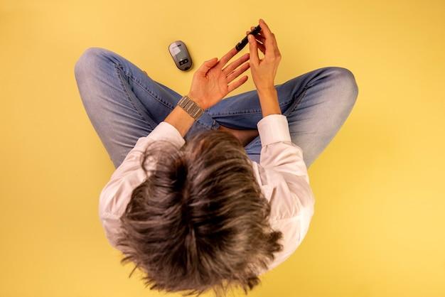 Mulher diabética sentada no chão usando aparelhos para medir a glicose no sangue.