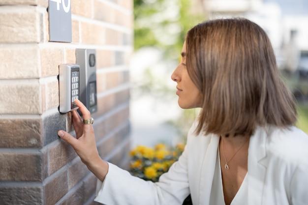 Mulher digita um código para acessar a porta de uma casa. conceito de tecnologia moderna e acesso sem chave ao apartamento
