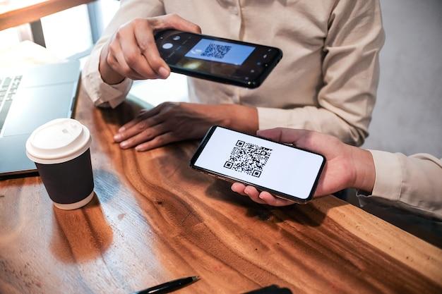 Mulher digitalizando o conceito de tecnologia sem dinheiro de compras online de código qr.