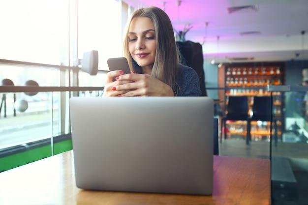 Mulher digitando a mensagem de texto no telefone inteligente em um café.