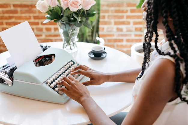 Mulher digitando em uma máquina de escrever retrô azul pastel