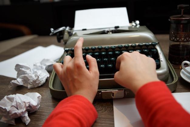 Mulher digitando em uma velha máquina de escrever