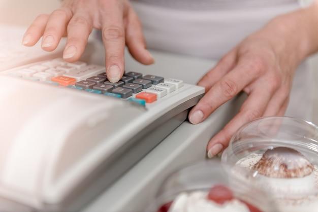 Mulher digitando na caixa registradora