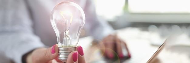 Mulher digitando no teclado do laptop e a lâmpada na mão, close-up