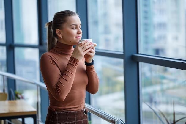 Mulher diretora sorridente e feliz pensando no desenvolvimento de sua carreira bem-sucedida, enquanto estava de pé com uma xícara de café aromático em seu escritório perto do fundo de uma janela com espaço de cópia