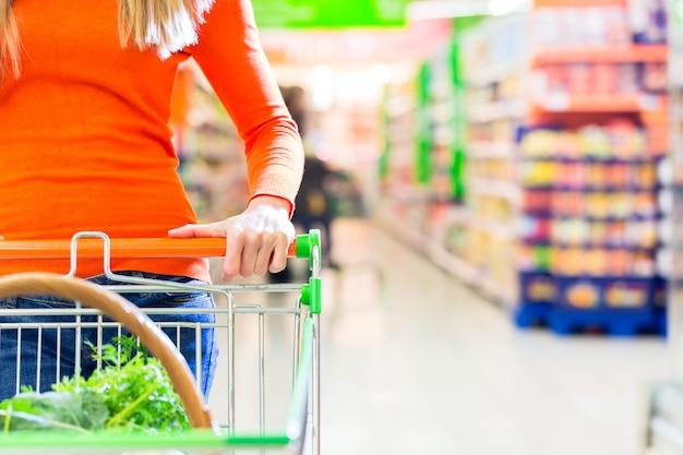 Mulher dirigindo carrinho de compras enquanto faz compras no supermercado