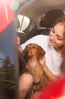 Mulher dirigindo com cachorro de perto