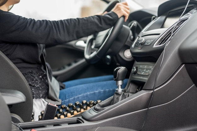 Mulher dirigindo o carro, com as mãos no volante, close up