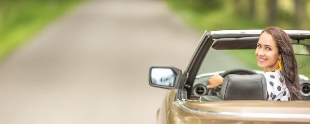 Mulher dirigindo um cabriolet olha para trás e sorri para a câmera.
