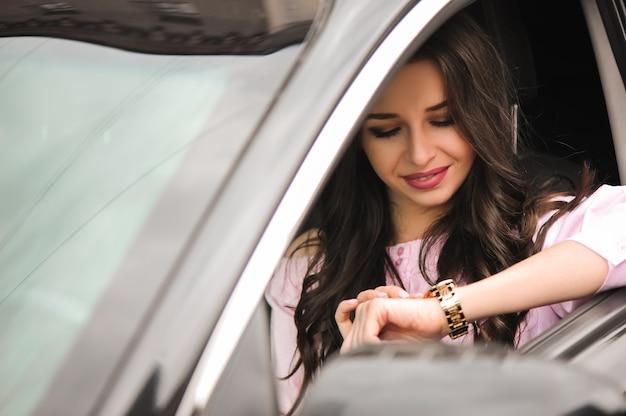 Mulher dirigindo um carro e olhando para o relógio.