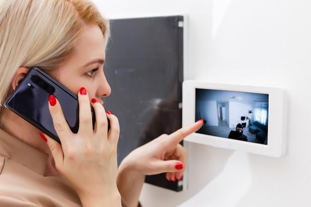 Mulher discando interfone, casa inteligente
