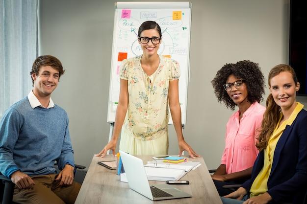 Mulher discutindo fluxograma no quadro branco com colegas de trabalho