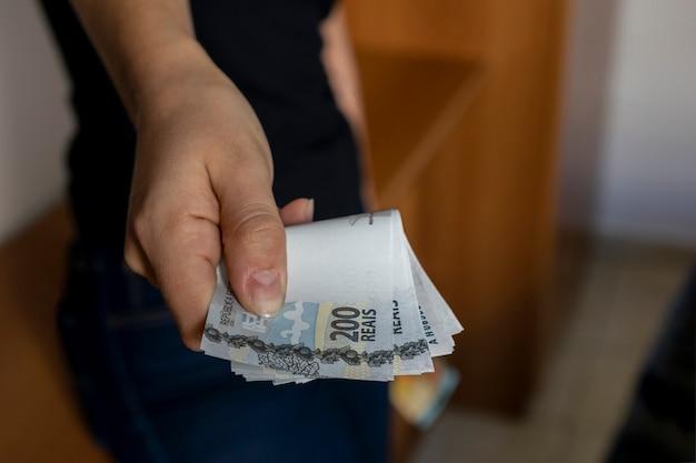 Mulher distribuindo novas notas de dinheiro brasileiras