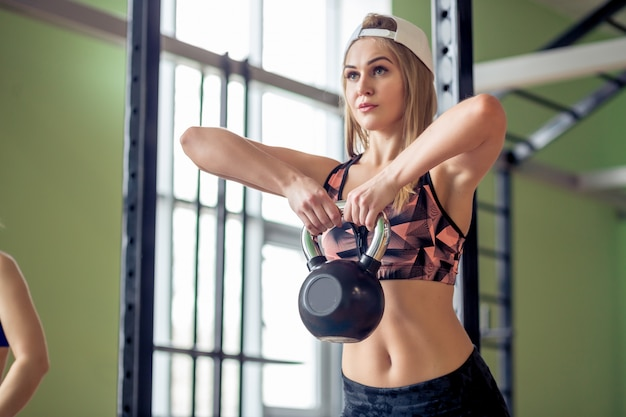 Mulher diversificada de pessoas malhando treinamento com kettlebells no ginásio industrial