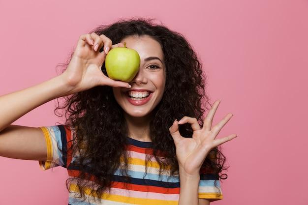 Mulher divertida de 20 anos com cabelo encaracolado sorrindo e segurando uma maçã verde isolada na rosa