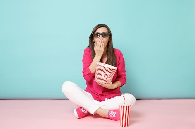 Mulher divertida de retrato de corpo inteiro com camisa rosa e calça branca sentada no chão assistindo filme