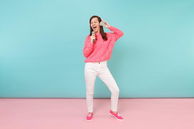 Mulher divertida de retrato de corpo inteiro em suéter de malha, calça branca, fones de ouvido cantando música no microfone