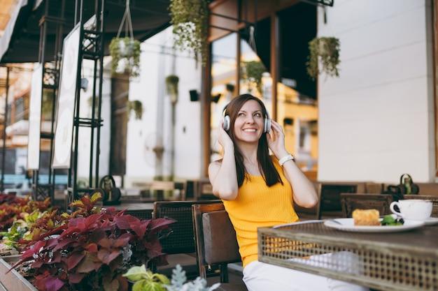 Mulher divertida em um café de rua ao ar livre, sentada à mesa com roupas amarelas, ouvindo música em fones de ouvido