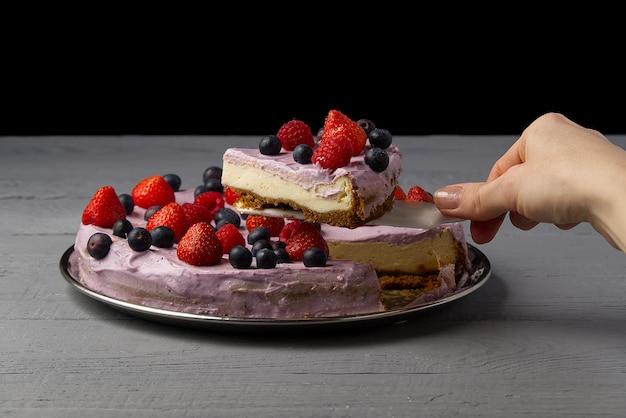 Mulher dividida cheesecake e tomar uma fatia para oferecê-lo. cheesecake caseiro com morango, mirtilo e framboesa.