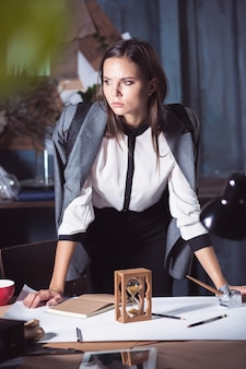 Mulher do arquiteto trabalhando na mesa de desenho no escritório ou em casa.