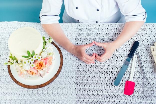 Mulher do chef confeiteiro mostra o símbolo do coração de dedos ao lado do bolo de aniversário de casamento de duas camadas branco cremoso com flores frescas na mesa no estúdio sobre fundo azul. o conceito de amor pelo trabalho