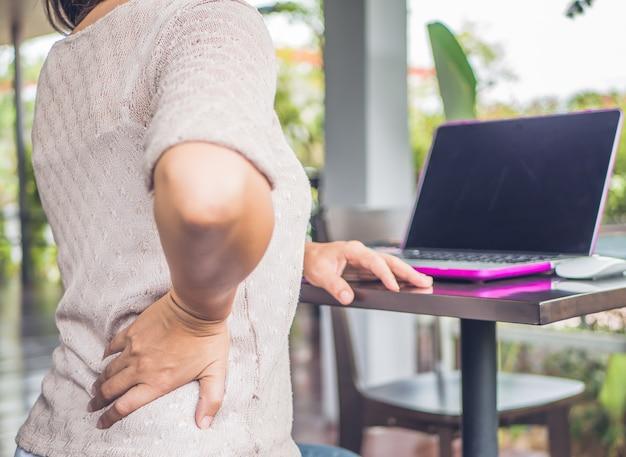 Mulher do close up com as mãos que mantêm sua cintura para trás na dor. síndrome de escritório =.