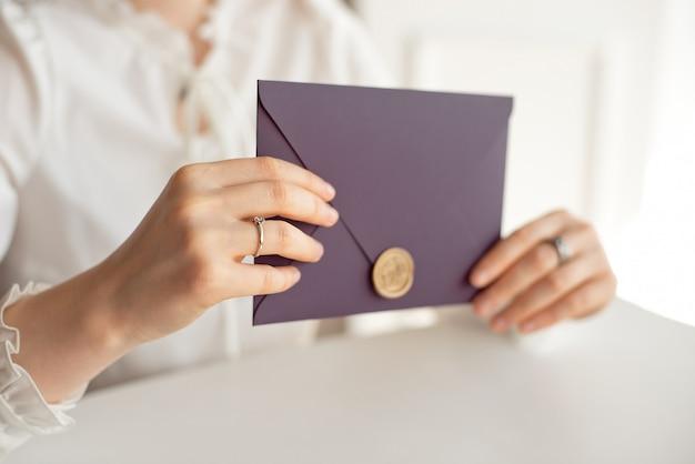 Mulher do close-up com o corpo magro que realiza nas mãos o cartão roxo do envelope da forma do quadrado da cor do cartão do convite.